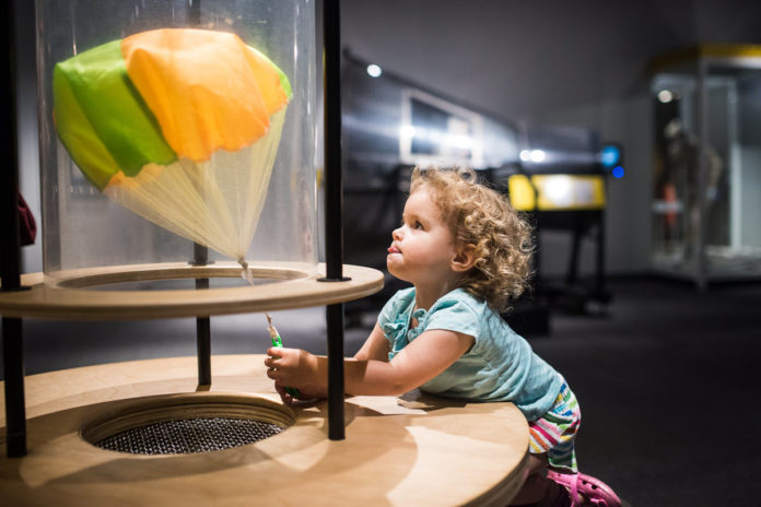 A child test a toy parachute at the Museum of Life and Science
