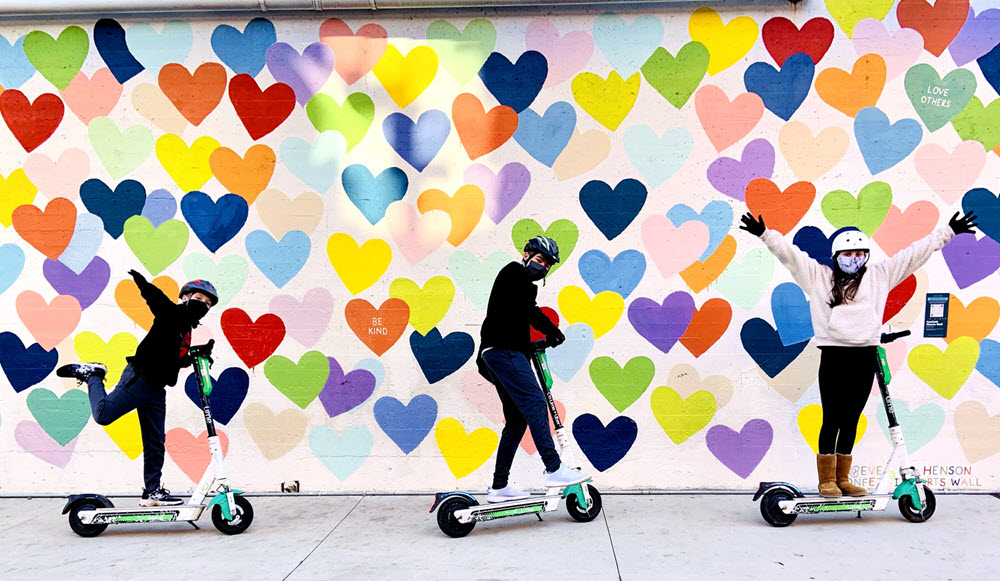 Kids on scooters pose in front of confetti heart wall in Charlotte